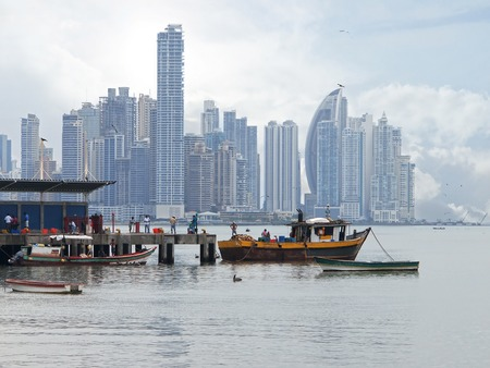 Wharf with fishing boats in foreground and skyscrapers in background of Panama City, Panama photo