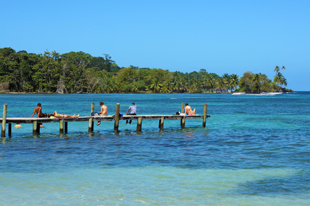 Tourists on a wooden dock over the Caribbean sea and tropical coast in Carenero island, Panama