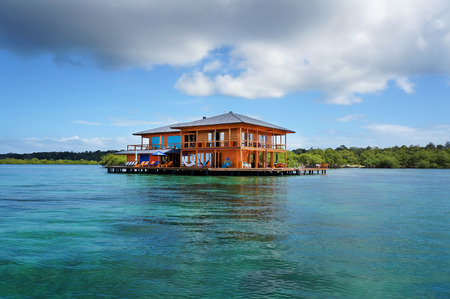 Beautiful house on stilts over water of the Caribbean sea with cloudy blue sky, Bocas del Toro, Panama