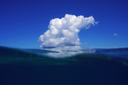 Blue sky and sea split by waterline with a cloud reflected on water surface of the Caribbean sea photo