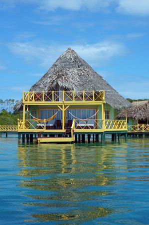 Tropical bungalow on stilts over water with palm thatched roof, Bocas del Toro, Caribbean sea, Central America, Panama