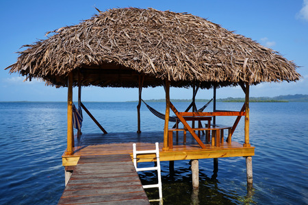 palapa: Tropical hut on stilts over water with thatched roof made of dried palm leaves, Caribbean sea