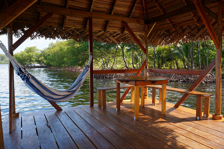 palapa: Peaceful scene on a palapa over water with hammock and a table, Caribbean sea