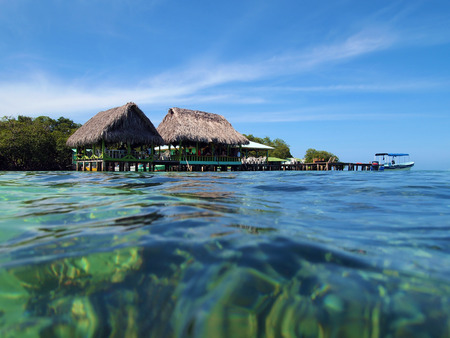 stilts: Tropical bar restaurant on stilts with thatched roof over the Caribbean sea, archipelago of Bocas del Toro, Panama