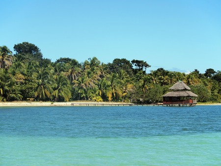 Tropical beach with coconut trees and a restaurant over the sea photo