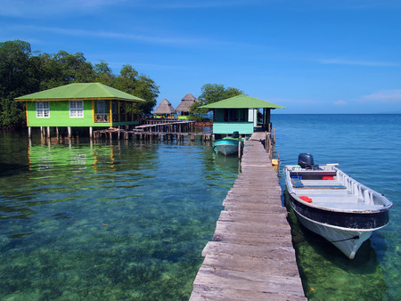 Tropical resort over the water with boat at dock and bungalows, Caribbean sea, Crawl Cay, Bocas del Toro, Panama