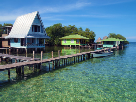 stilts: Caribbean resort over the sea with wooden dock and bungalows on stilts, Crawl Cay, Bocas del Toro, Panama Stock Photo