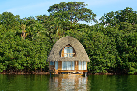 Tropical bungalow over water with thatched palm roof and lush vegetation in background, Bocas del Toro, Caribbean sea, Central America, Panama photo