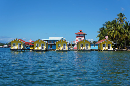 colon panama: Tropical vacation bungalows over water with coconut trees on the Caribbean sea, Bocas del toro, Carenero island, Panama Stock Photo