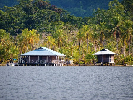 beach front: Tropical coastal house over the water with bungalow on stilts and lush jungle in background, Caribbean sea, Bocas del Toro, Panama Stock Photo