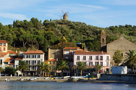 vermilion coast: Beach hotel in Collioure village with a windmill at the top of the hill, Roussillon, Vermilion coast, Pyrenees Orientales, France