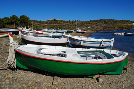 Traditional Spanish fishing boats on a beach of the Mediterranean sea, Cadaques, Costa Brava, Spain photo