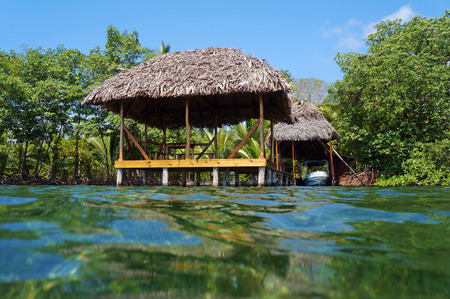 boathouse: Tropical hut with thatch roof overwater and a boathouse with vegetation in background, viewed from water surface, Caribbean sea