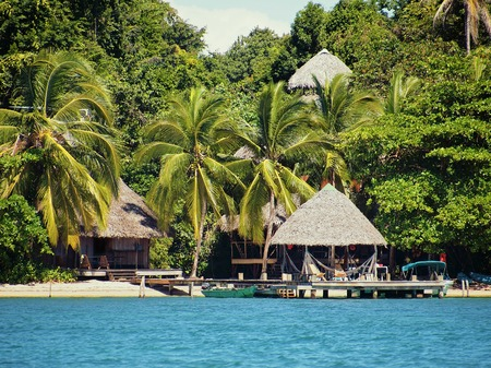 Eco resort on a Caribbean beach with thatched huts and lush tropical vegetation, Bocas del Toro, Panama Banque d'images