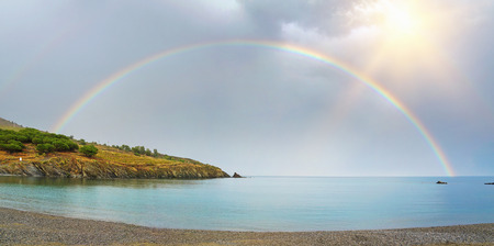 vermilion coast: panorama of a rainbow, half over sea and land viewed from the pebble beach of Bernardi in the Mediterranean bay of Paulilles, Roussillon, Pyrenees Orientales, France