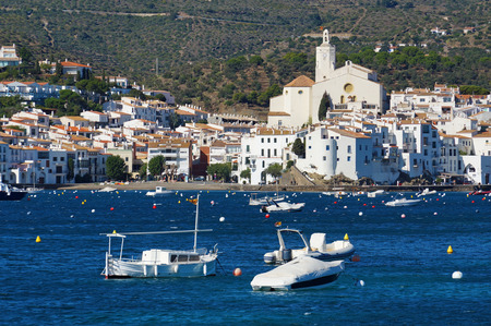 alt: village of Cadaques on the Mediterranean coast with boats on mooring buoys in foreground, Catalonia, Costa Brava, Spain