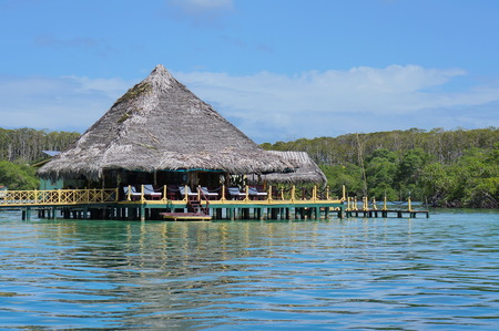 stilt: Tropical restaurant with thatch roof over water of the Caribbean sea, Central America Editorial