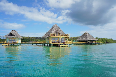thatched: Tropical resort over water with thatched roof bungalow, Caribbean sea Editorial