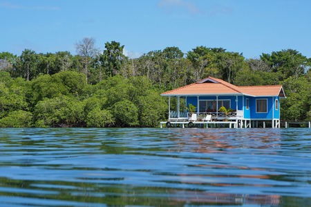 colon panama: Overwater bungalow with vegetation in background viewed from sea surface, Caribbean, Panama
