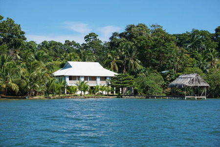 waterfront property: Oceanfront property with a Caribbean house and a tropical hut over the water, Bocas del Toro, Panama, Central America