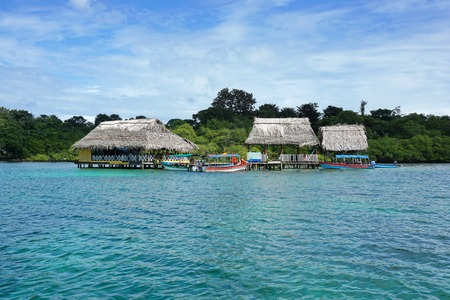 bocas del toro: Tropical restaurant with thatched roof over the water and boats at dock, Caribbean, Bocas del Toro, Central America, Panama