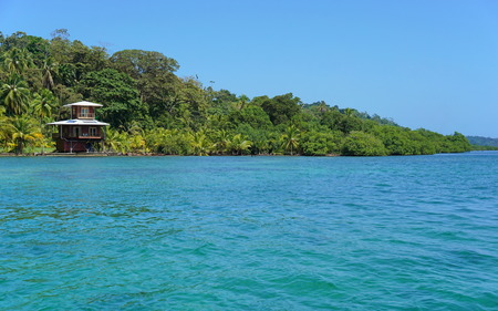 oceanfront: Off-grid oceanfront house and lush tropical vegetation on the coast of the Caribbean island of Bastimentos, Bocas del Toro, Panama, Central America