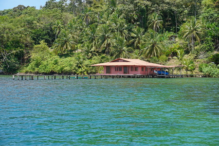 bocas del toro: Lush tropical coast with an house and dock over the water in the archipelago of Bocas del Toro, Panama Editorial