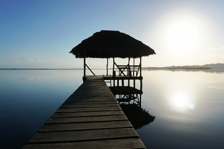 horizon over water: Dock with tropical hut over the water and calm sea surface with sunrise light, Caribbean, Panama, Central America Stock Photo