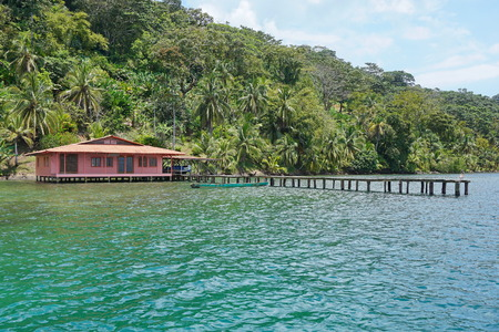 bocas del toro: Tropical house with dock over the sea and luxuriant tropical vegetation on the land, Caribbean coast of Panama, Bocas del Toro