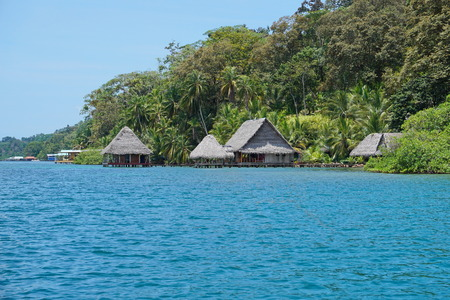 bocas del toro: Eco lodge with thatched huts over the water and lush tropical vegetation on Caribbean coast of Panama, Bocas del Toro