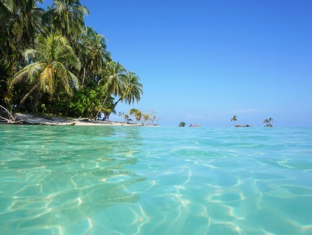 turquoise water: Sea surface with turquoise water and lush tropical island shore with coconut trees, Caribbean, Panama Stock Photo