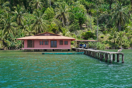 bocas del toro: Tropical home over the sea with pelican on its dock and lush vegetation on the shore, Caribbean, Bocas del Toro, Panama, Central America