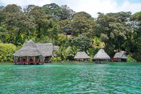 luxuriant: Waterfront ecolodge with thatched hut overwater and luxuriant tropical vegetation on the land Caribbean side of Panama Central America