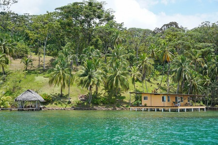 oceanfront: Oceanfront Caribbean property in Central America with coconut palm trees and a house with hut over water Panama Bocas del Toro Editorial