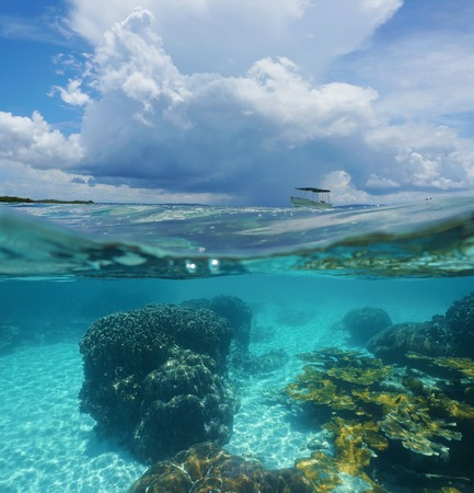 halves: Split image with corals underwater and threatening cloud with a boat above waterline Caribbean sea Panama