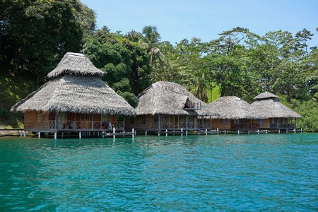 パナマ ボカスデルトロ中央アメリカのカリブ海の海の水の上のわらぶき屋根のバンガローと熱帯エコ リゾート