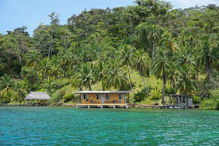 oceanfront: Tropical oceanfront property in Panama with lush vegetation and house with hut over water Caribbean sea Central America