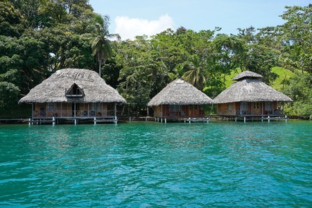 bocas del toro: Tropical shore with thatched bungalows over the water on the Caribbean coast of Panama, Bocas del Toro, Central America
