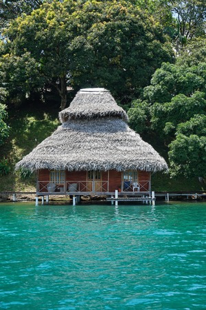 thatched roof: Tropical wooden bungalow with thatched roof over water of the Caribbean sea in Central America, Panama, Bocas del Toro Stock Photo