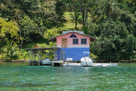 boat house: Coastal home with floating dock and boat house over water on the Caribbean shore of Panama, Central America