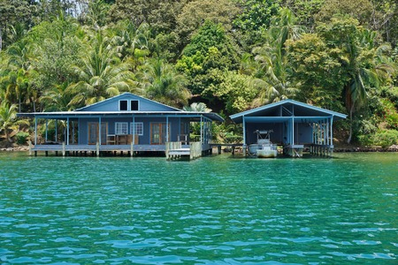 boat house: Tropical home and boat house over the sea with lush vegetation on the shore, Panama, Central America