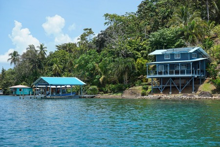 bocas del toro: Off grid waterfront home on lush tropical coast with boat at dock on an island of the archipelago of Bocas del Toro, Panama