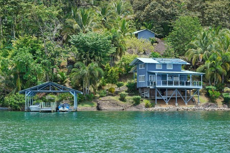 waterfront property: Coastal property on lush tropical shore with boats at dock and an house, Caribbean sea, Panama, Central America