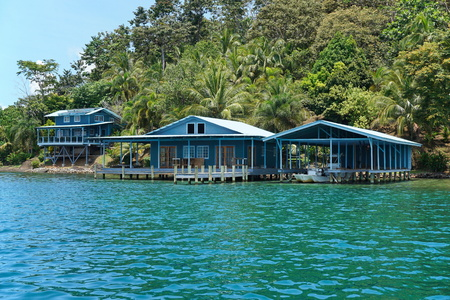 boat house: Caribbean home and boat house over the water with lush tropical vegetation on the coast, Panama, Central America