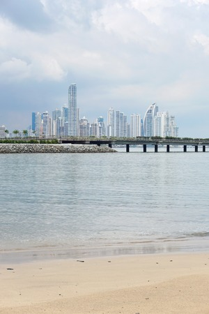 panama city beach: Sandy beach with the new highway over the bay and skyscrapers of business center of Panama city in background, Panama, Central America