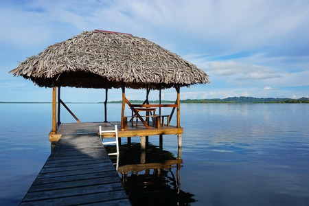 palapa: Palapa hut over the water with thatched palm roof in a calm lagoon, Caribbean sea, Central America, Panama Stock Photo