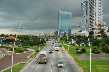 panama city: Cars and trucks on the highway in Panama City with buildings and cloudy sky in the background, Panama, Central America