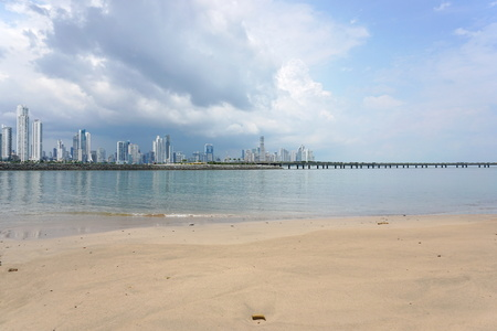 panama city: Sandy beach with the new highway over the bay and the skyscrapers of Panama city in background, Panama, Central America Stock Photo