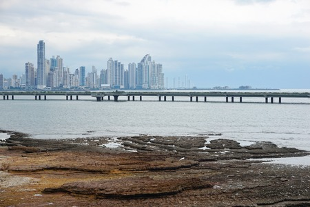 panama city: Rocky shore in foreground with the new highway over the ocean and the skyscrapers of the business center of Panama city in background, Panama, Central America