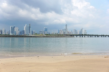 panama city beach: Beach sand in foreground with the new highway over the bay and Panama city skyscrapers in background, Panama, Central America Stock Photo
